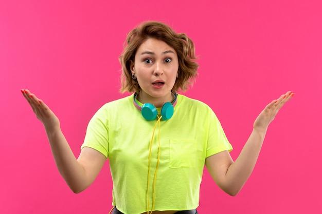 Een vooraanzicht jonge mooie dame in zuurkleurige overhemd zwarte broek met blauwe oortelefoons verrast
