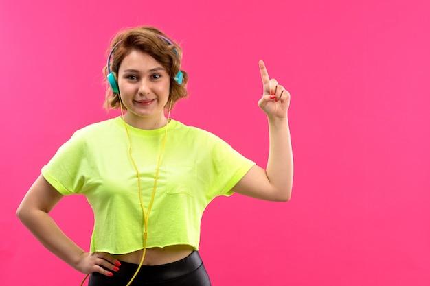 Een vooraanzicht jonge mooie dame in zuurkleurige shirt zwarte broek met blauwe koptelefoon luisteren naar muziek glimlachen