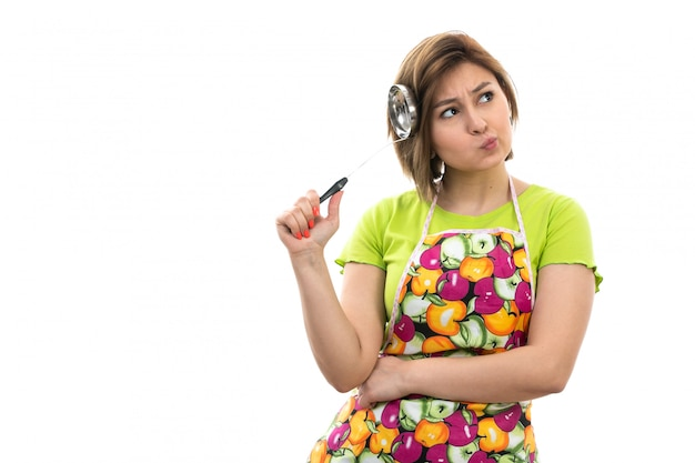 Een vooraanzicht jonge mooie huisvrouw die in groene overhemds kleurrijke kaap grote zilveren lepel houden denkend op de witte achtergrondhuis schoonmakende keuken