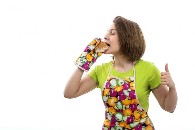 Een vooraanzicht jonge mooie huisvrouw die in groene overhemds kleurrijke kaap smakelijke baksels houden die proevend op de witte achtergrondhuis vrouwelijke keuken eten