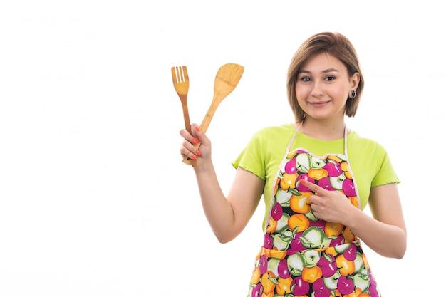 Een vooraanzicht jonge mooie huisvrouw in groene overhemd kleurrijke kaap het glimlachen toestel van de holdings houten keuken op de witte achtergrondhuis schoonmakende keuken