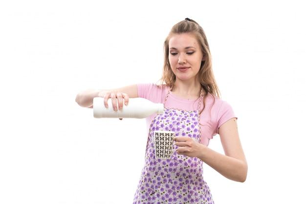 Een vooraanzicht jonge mooie huisvrouw in roze shirt kleurrijke cape gelukkig lachend gietend water