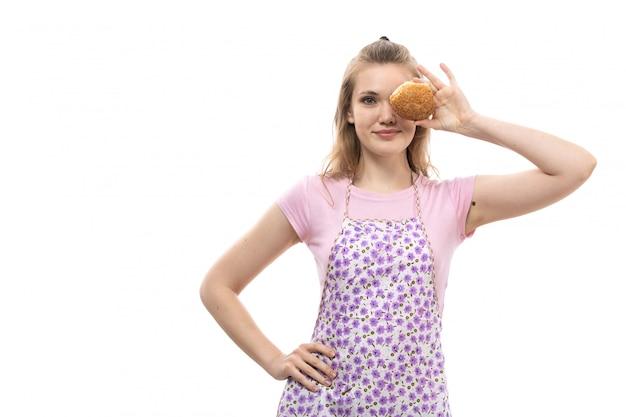 Een vooraanzicht jonge mooie huisvrouw in roze shirt kleurrijke cape houden en die haar oog met weinig brood lachend