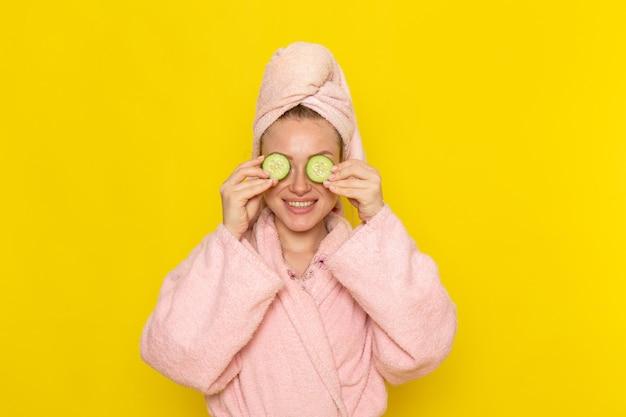 Een vooraanzicht jonge mooie vrouw in roze badjas die haar ogen bedekt met plakjes komkommer met een glimlach