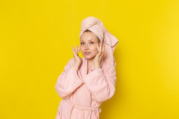 Een vooraanzicht jonge mooie vrouw in roze badjas gezichtscrème wrijven