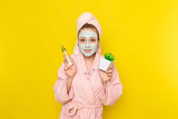 Een vooraanzicht jonge mooie vrouw in roze badjas met make-up schonere spray en plantje