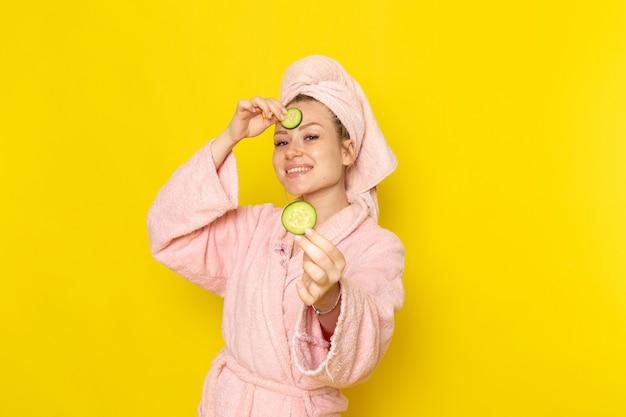 Een vooraanzicht jonge mooie vrouw in roze badjas met plakjes komkommer en lachend
