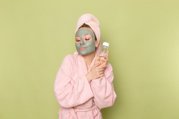 Een vooraanzicht jonge mooie vrouw in roze badjas met spray kolf