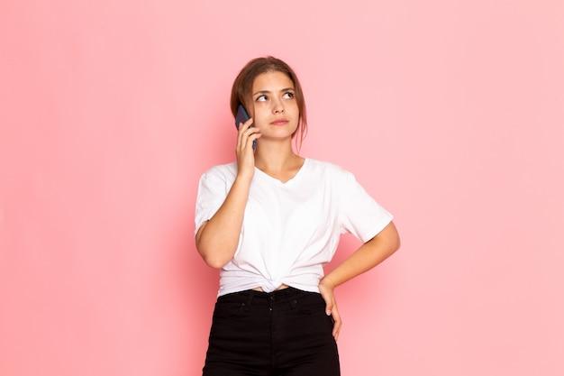 Een vooraanzicht jonge mooie vrouw in wit overhemd praten aan de telefoon