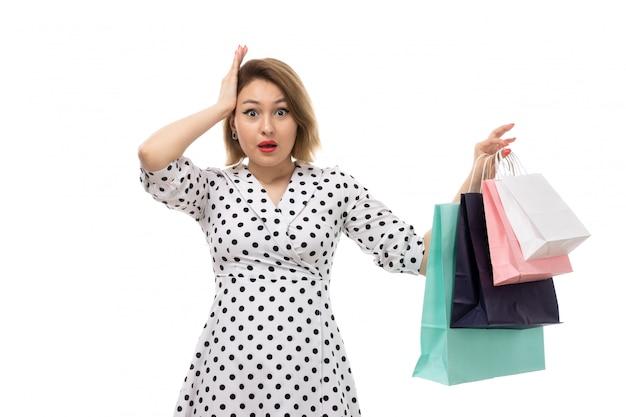 Een vooraanzicht jonge mooie vrouw in zwart-witte stipkleding die het winkelen pakketten verrast houdt