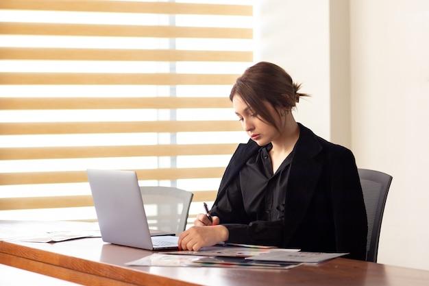 Een vooraanzicht jonge mooie zakenvrouw in zwart shirt zwart jasje met behulp van haar zilveren laptop schrijven lezen werken binnen haar kantoor werk baan bouwen