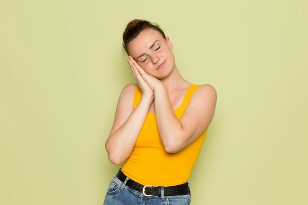 Een vooraanzicht jonge vrouw in geel shirt en spijkerbroek met slapen pose