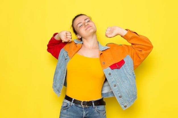 Een vooraanzicht jonge vrouw in gele overhemd kleurrijke jas en blauwe jeans niezen