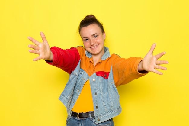 Een vooraanzicht jonge vrouw in gele overhemd kleurrijke jas en blauwe spijkerbroek met wijd open armen en glimlach een haar gezicht