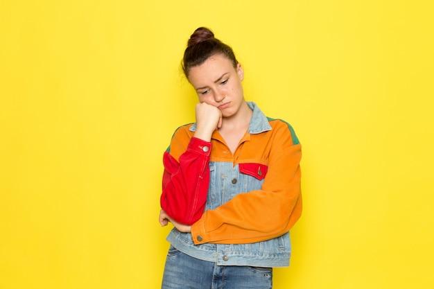 Een vooraanzicht jonge vrouw in gele overhemd kleurrijke jas en spijkerbroek met denken expressie