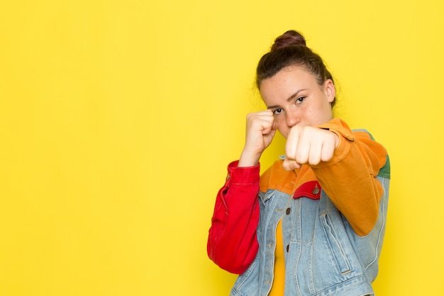 Een vooraanzicht jonge vrouw in gele overhemd kleurrijke jas en spijkerbroek poseren met boksen staan