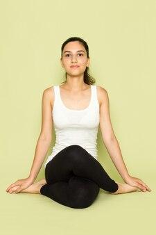 Een vooraanzicht jonge vrouw in wit overhemd en zwarte broek poseren zittend in mediterende yoga pose