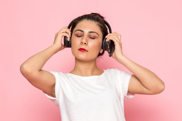 Een vooraanzicht jonge vrouw in wit t-shirt en spijkerbroek luisteren naar muziek
