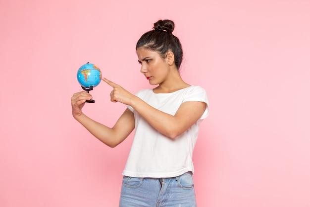 Een vooraanzicht jonge vrouw in wit t-shirt en spijkerbroek met kleine wereldbol