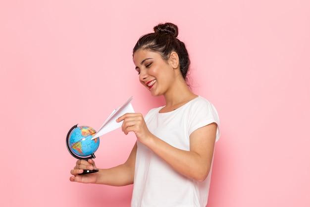 Een vooraanzicht jonge vrouw in wit t-shirt en spijkerbroek met papieren vliegtuigje en kleine wereldbol