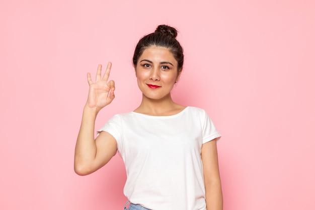 Een vooraanzicht jonge vrouw in wit t-shirt en spijkerbroek poseren met opgetogen uitdrukking