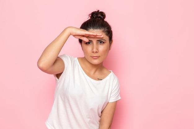Een vooraanzicht jonge vrouw in wit t-shirt en spijkerbroek poseren op zoek in de verte