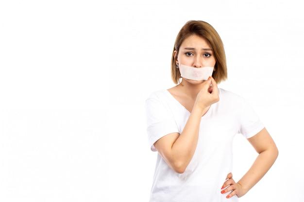 Een vooraanzicht jonge vrouw in wit t-shirt met wit verband rond haar mond aanraken van haar verband op de witte