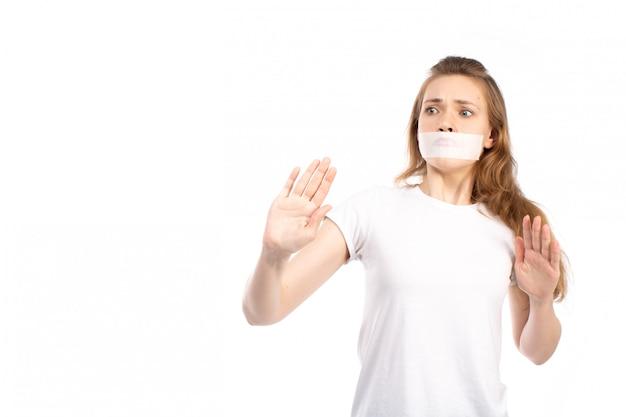 Een vooraanzicht jonge vrouw in wit t-shirt met wit verband rond haar mond bang voorzichtig op het wit