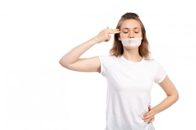 Een vooraanzicht jonge vrouw in wit t-shirt met wit verband rond haar mond wijzende vingers in haar hoofd op de witte