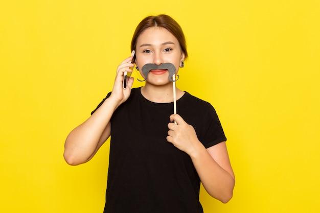 Een vooraanzicht jonge vrouw in zwarte jurk poseren met nep snor en praten over de telefoon lachend op geel