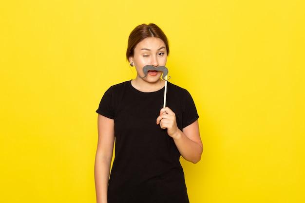 Een vooraanzicht jonge vrouw in zwarte jurk poseren met valse snor met grappige uitdrukking op geel