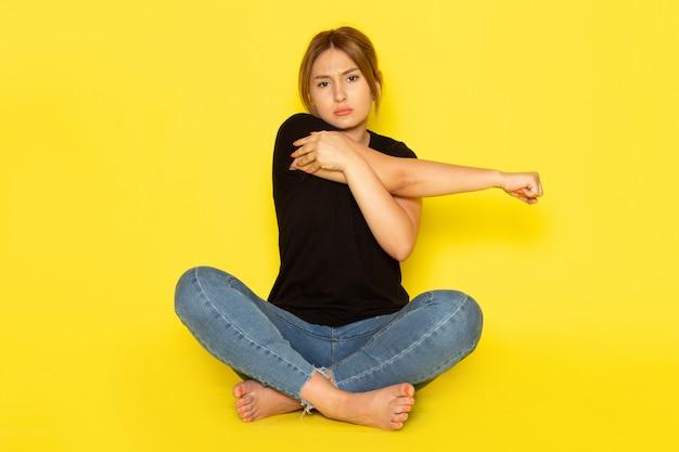 Een vooraanzicht jonge vrouw zit in zwart shirt en spijkerbroek poseren met pijn als gevolg van handschade op geel
