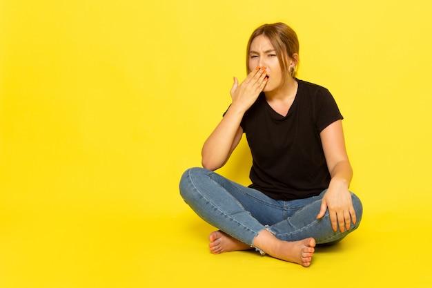 Een vooraanzicht jonge vrouw zitten in zwart shirt en spijkerbroek niezen op geel