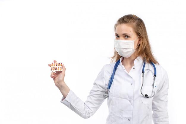 Een vooraanzicht jonge vrouwelijke arts in wit medisch kostuum met stethoscoop die witte beschermende pillen van de masker stellende holding op het wit dragen