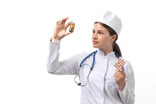 Een vooraanzicht jonge vrouwelijke arts in witte medische pak en witte dop met blauwe stethoscoop met pillen en drankjes