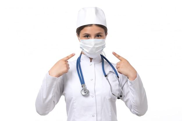 Een vooraanzicht jonge vrouwelijke arts in witte medische pak met blauwe stethoscoop dragen wit masker