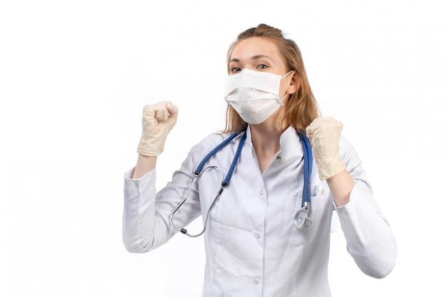 Een vooraanzicht jonge vrouwelijke arts in witte medische pak met stethoscoop dragen witte beschermend masker in handschoenen aan de witte