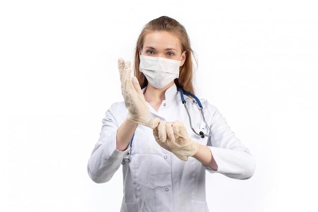 Een vooraanzicht jonge vrouwelijke arts in witte medische pak met stethoscoop dragen witte beschermend masker met handschoenen aan de witte