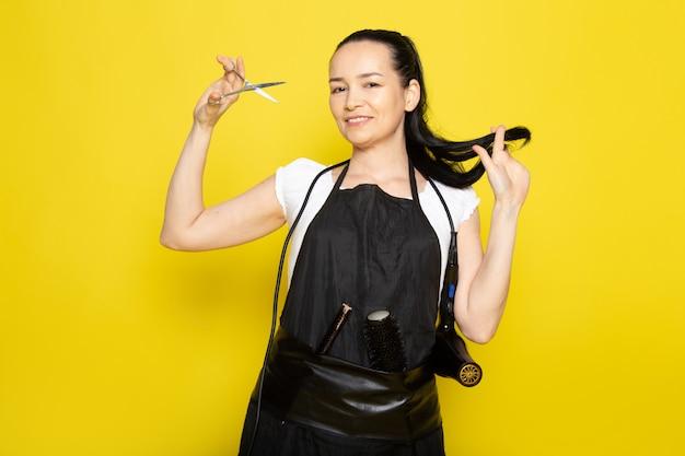 Een vooraanzicht jonge vrouwelijke kapper in witte t-shirt zwarte cape snijden haar haar glimlachend poseren
