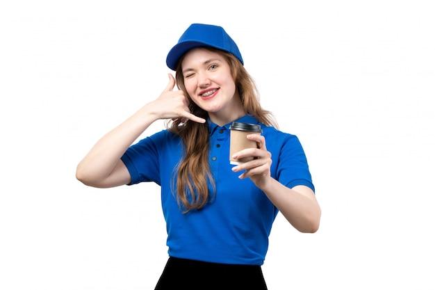 Een vooraanzicht jonge vrouwelijke koerier in blauw overhemd blauw glb glimlachend tonend telefoongesprek teken houden koffiekopje op wit