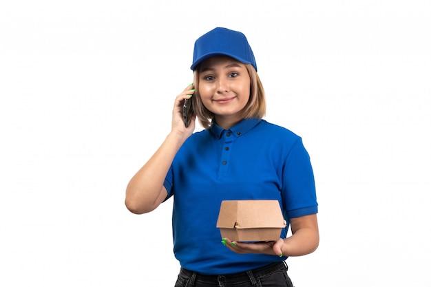 Een vooraanzicht jonge vrouwelijke koerier in blauw uniform bedrijfstelefoon en voedselbezorgingspakket
