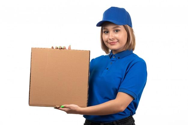 Een vooraanzicht jonge vrouwelijke koerier in blauw uniform de leveringspakket van het holdingsvoedsel