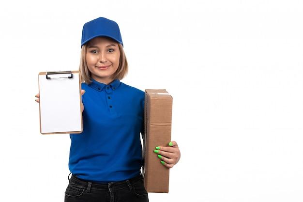 Een vooraanzicht jonge vrouwelijke koerier in blauw uniform met voedselbezorgingspakket en blocnote voor handtekeningen