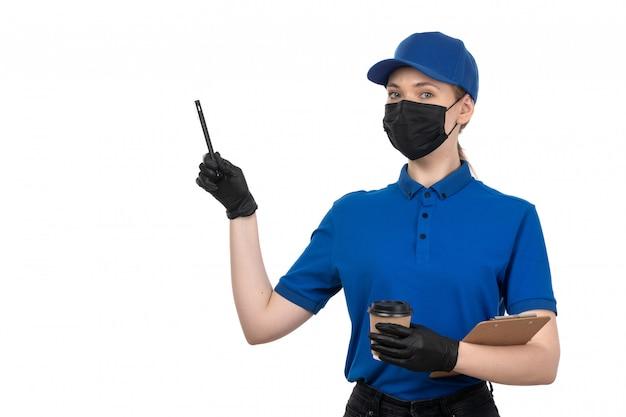 Een vooraanzicht jonge vrouwelijke koerier in blauw uniform zwart masker en handschoenen met koffiekopje en blocnote