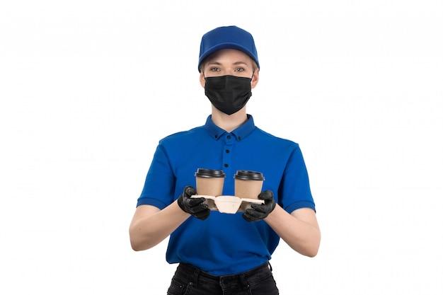 Een vooraanzicht jonge vrouwelijke koerier in blauw uniform zwart masker en handschoenen met koffiekopjes