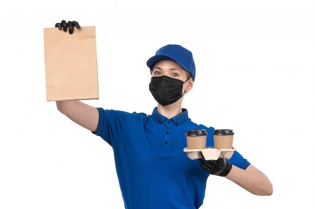 Een vooraanzicht jonge vrouwelijke koerier in blauw uniform zwart masker en handschoenen met koffiekoppen en pakket