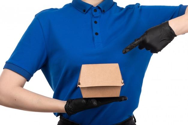 Een vooraanzicht jonge vrouwelijke koerier in blauw uniform zwart masker en handschoenen met voedsel levering pakket