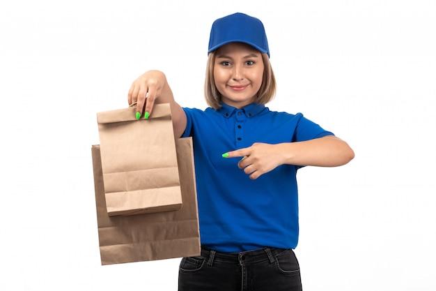 Een vooraanzicht jonge vrouwelijke koerier in blauwe uniforme voedselbezorgingspakketten