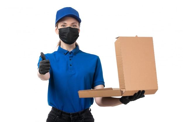 Een vooraanzicht jonge vrouwelijke koerier in blauwe uniforme zwarte handschoenen en zwart masker met voedselbezorgingspakket