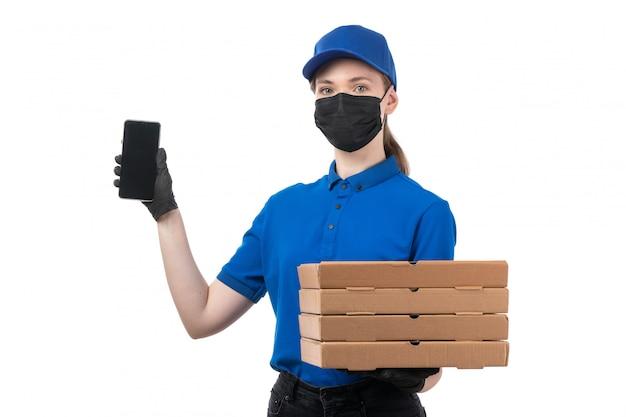 Een vooraanzicht jonge vrouwelijke koerier in blauwe uniforme zwarte handschoenen en zwart masker met voedselbezorgingspakketten en smartphone